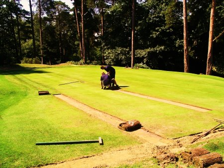 Foxhills greenkeepers relaying turf on the drains on the 9th Green